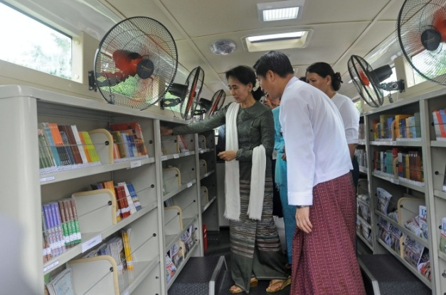 Myanmar democracy leader Aung San Suu Kyi (L) looks at books displayed on a mobile library bus during a ceremony to open the service in Kawhmu township, on outskirts of Yangon on July 27, 2013. The first and only mobile library service in country and over 15,000 books will be avaliable on the bus. AFP PHOTO/Soe Than WIN